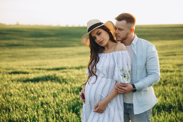 Husband And His Pregnant Wife Are Walking At Sunset In Field On The Outside Theme Romantic Pregnancy Outdoors Premium Photo