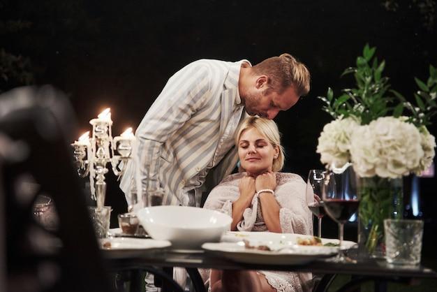 夫は妻にキスします。美しい大人のカップルは夜の時間に豪華なディナーを持っています 無料写真