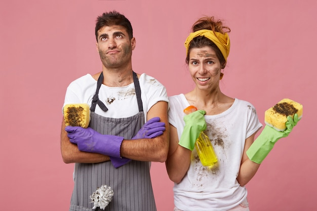 Husband wearing apron and gloves holding sponge looking fatigued up Free Photo