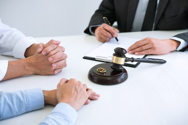 Husband and wife during divorce process with lawyer and signing of divorce contract Premium Photo