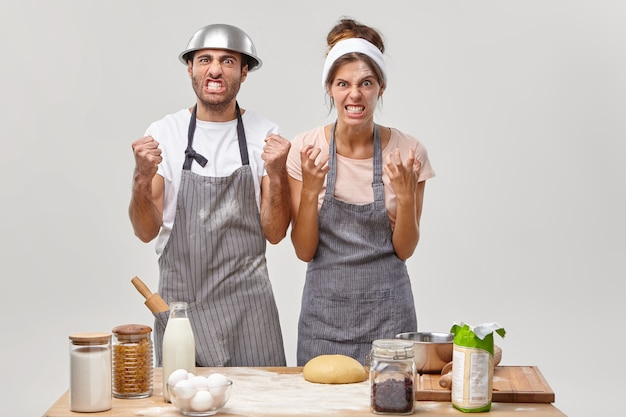 Husband and wife pose in the kitchen preparing tasty dinner Free Photo