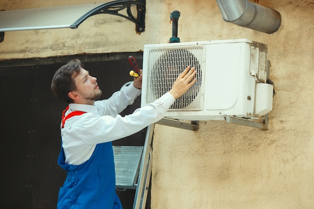 Hvac technician working on a capacitor part for condensing unit. male worker or repairman in uniform repairing and adjusting conditioning system, diagnosing and looking for technical issues. Free Photo