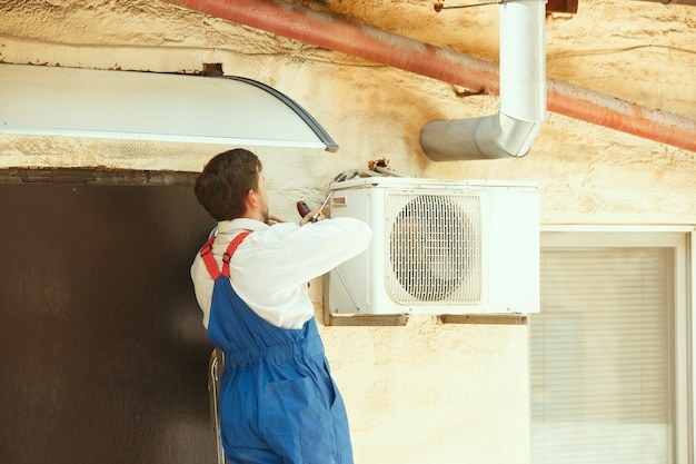 Hvac technician working on a capacitor part for condensing unit Free Photo