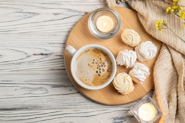 Hygge composition with coffee, candles, marshmallows and knitted plaid Premium Photo