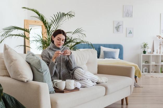 居心地の良いインテリアhyggeのソファーに座っている暖かい灰色のセーターニットの女の子 Premium写真