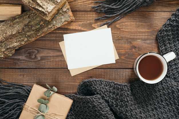 Композиция в стиле hygge с книгой, чашкой кофе, модным вязаным шарфом, дровами Premium Фотографии