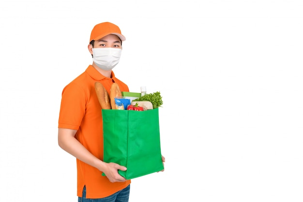 Hygienic man wearing medical mask carrying supermarket grocery shopping bag offering home delivery service isolated in white Premium Photo