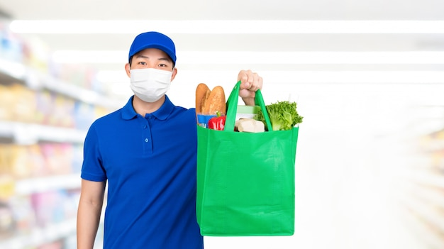 Hygienic man wearing medical mask holding grocery shopping bag in supermarket offering home delivery service Premium Photo