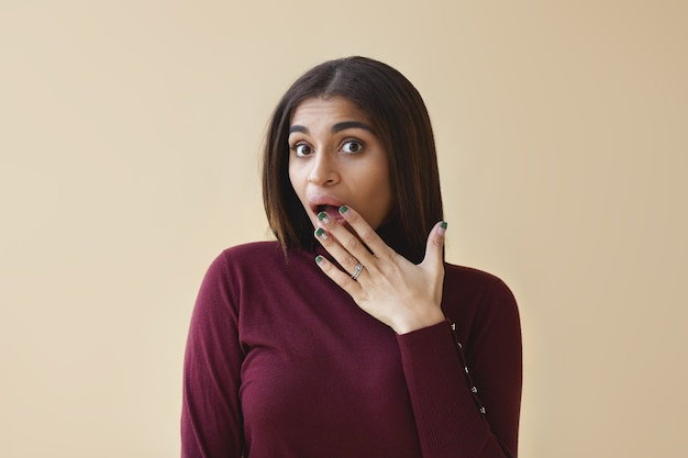 Non ci posso credere. giovane donna dalla pelle scura stupita con uno sguardo divertente e stupito, che copre la bocca aperta con la mano, scioccata da intriganti pettegolezzi succosi. espressioni facciali umane Foto Gratuite