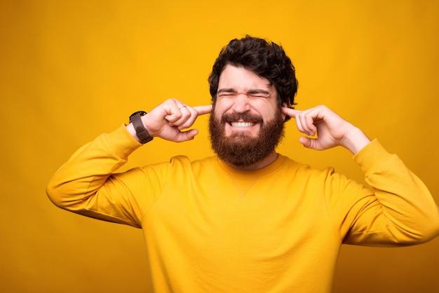 Я не хочу это слышать. бородатый мужчина закрывает уши пальцами. Premium Фотографии