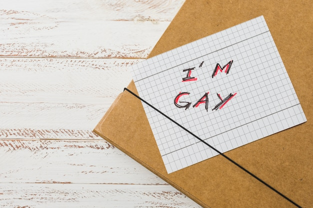 I gay inscription on paper against document case Free Photo