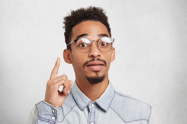 私は素晴らしい考えを得ます。自信を持って混血の男性科学者はめがねをかけ、口ひげとあごひげを持ち、指を上に上げ、 無料写真