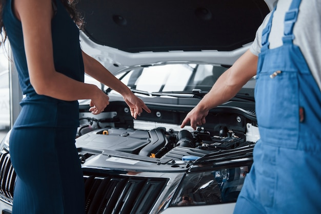 I guess your problem in that part. woman in the auto salon with employee in blue uniform taking her repaired car back Free Photo