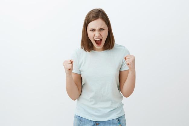 Odio le regole. ritratto di giovane donna arrabbiata e arrabbiata con i capelli corti castani che guarda da sotto la fronte accigliata e imbronciata stringendo i pugni dalla rabbia e dal furore che perde la pazienza sul muro grigio Foto Gratuite