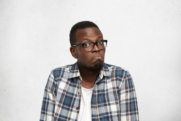 何も思いつきません。彼の唇をめちゃくちゃにして、躊躇して疑わしい顔つきで肩をすくめて眼鏡をかけている混乱している若いアフリカ系アメリカ人男性の肖像画。人間の顔の表情と感情 無料写真