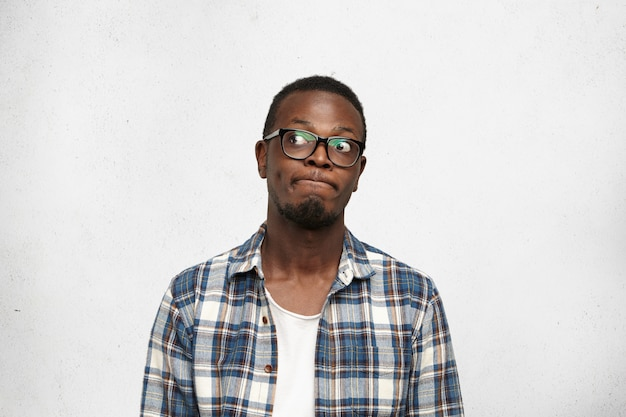 I don't know. clueless funny young dark-skinned male wearing stylish glasses pursuing lips and looking sideways with doubtful and uncertain expression, feeling indecisive about his future plans Free Photo