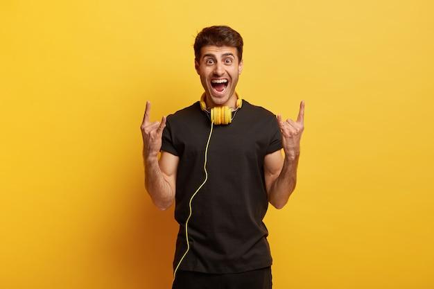 ヘビーメタルが好き!うれしそうな若い男性は狂っていて、両手でホーンジェスチャーをし、ヘッドフォンで好きな音楽を聴きます 無料写真