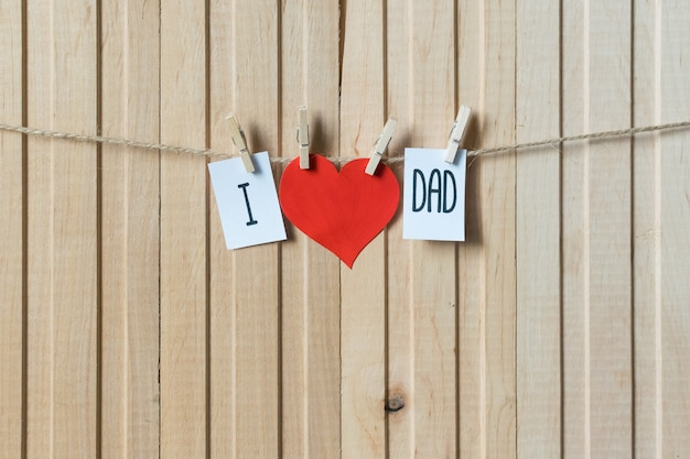I love dad. fathers day concept. message with paper heart hanging with pins over light wooden board. Premium Photo
