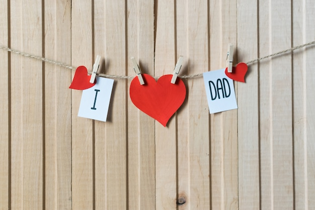 I love dad. fathers day concept. message with paper hearts hanging with pins over light wooden board. Premium Photo