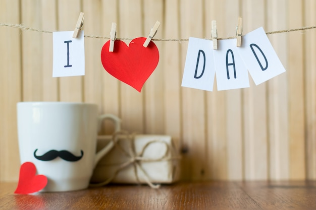 I love dad. fathers day greeting. message with paper heart hanging with clothespins over wooden board. Premium Photo