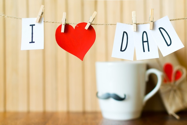 I love dad. fathers day message with paper heart hanging with clothespins over wooden board. Premium Photo