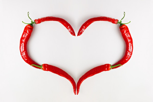 I love red chili pepper, heart shape on white wooden table, top view Premium Photo