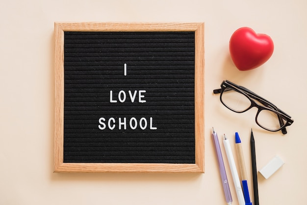 I love school text on slate near pens; eraser; eyeglasses and red heart over plain background Free Photo