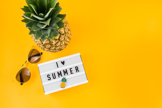 I love summer light box; sunglasses and pineapple on yellow background Free Photo
