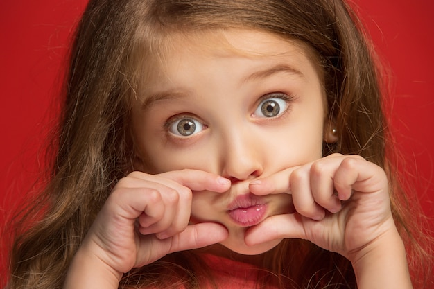 わたしは、あなたを愛しています。トレンディな赤いスタジオの背景に孤立した笑顔、立っている幸せな十代の少女。 無料写真