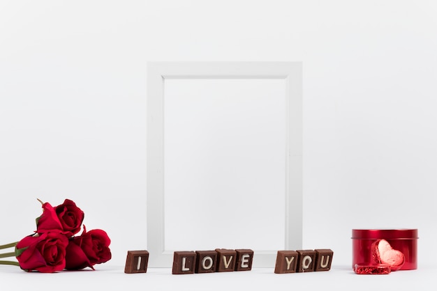 I love you inscription on chocolate pieces near photo frame, flowers and box Free Photo