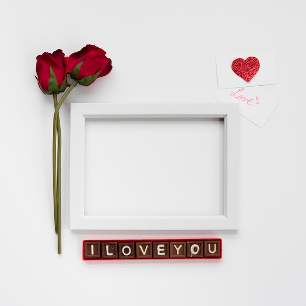 I love you inscription on chocolate pieces near photo frame, flowers and cards Free Photo