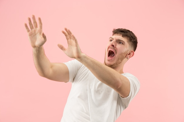 I'm afraid. fright. portrait of the scared man. business man standing isolated on trendy pink studio background. male half-length portrait. human emotions, facial expression concept Free Photo