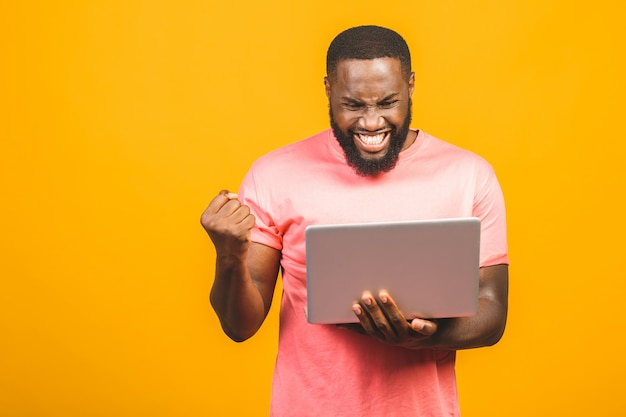 I'm winner! excited happy afro american man looking at laptop computer screen and celebrating the win isolated over yellow background. Premium Photo