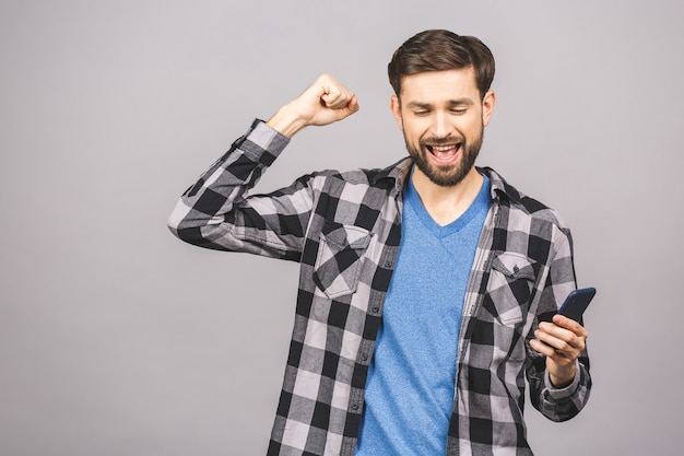 I'm a winner! happy man holding smartphone and celebrating his success isolated over grey wall. Premium Photo