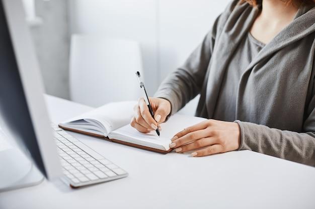 私は昔ながらの書き方を好みます。ノートブックでメモを作成し、オフィスでの勤務中にコンピューター画面を見て、集中して割り当てに集中しようとする忙しい女性のトリミングされた肖像画 無料写真
