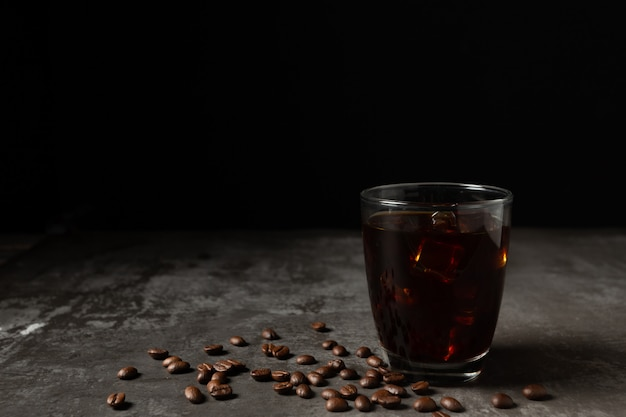 Ice black coffee in a glass on the wooden table. Free Photo