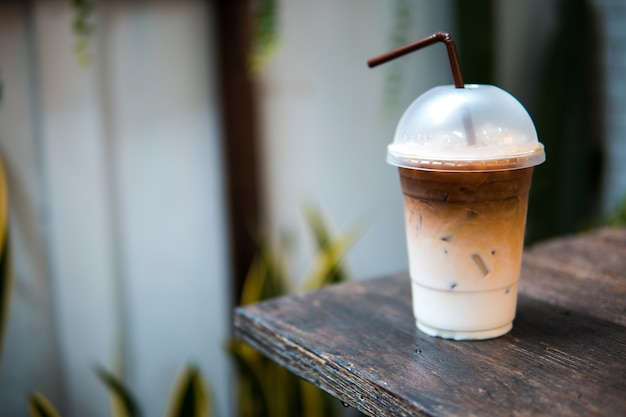 Ice coffee with drinking straw on wood table Premium Photo