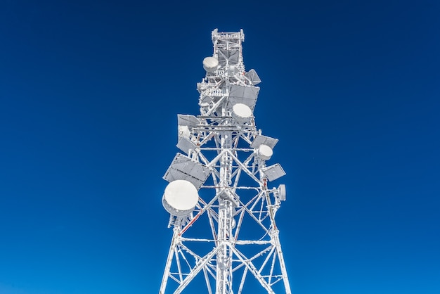 Ice-covered cell tower on the roof of the base radio station located in the highlands. cellular phone station. Premium Photo