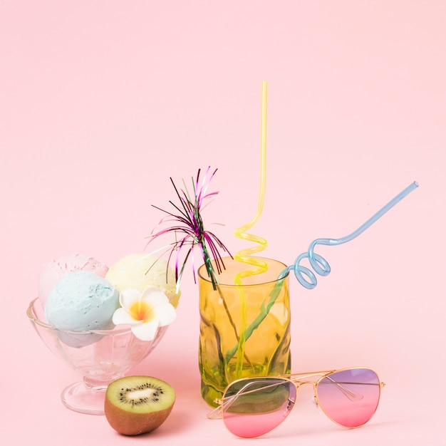 Ice cream balls on bowl near sunglasses and glass with ornamental wand and straws Free Photo