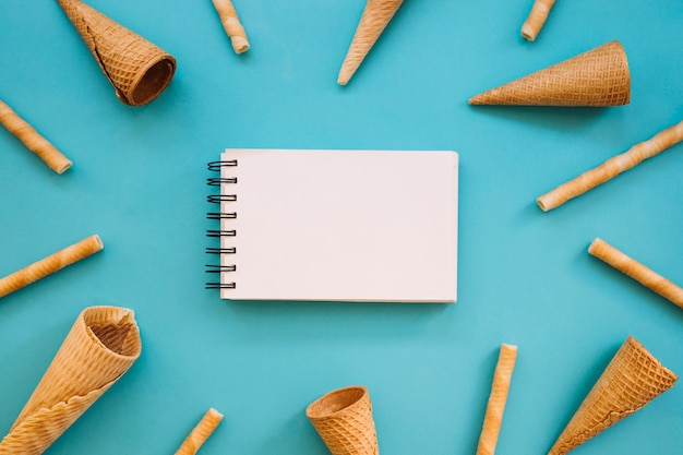 Ice cream concept with notepad and cones Free Photo