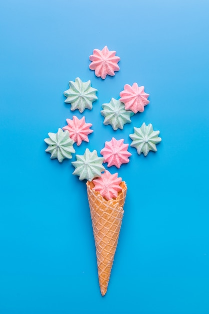Ice cream cone with meringues on blue Premium Photo
