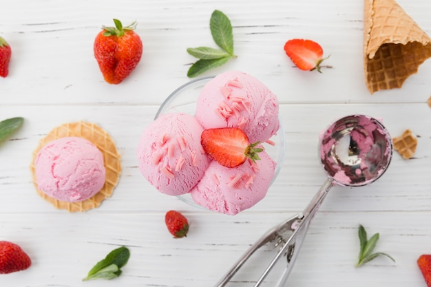 Ice cream in glass with strawberry on wooden table Free Photo