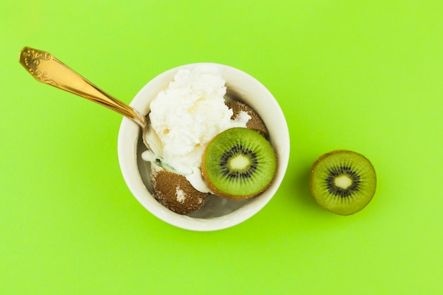 Ice cream near spoon and kiwi in bowl Free Photo