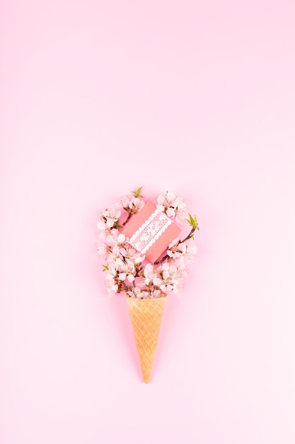 Ice cream waffle cone with colorful flowers and gift box on pink Premium Photo