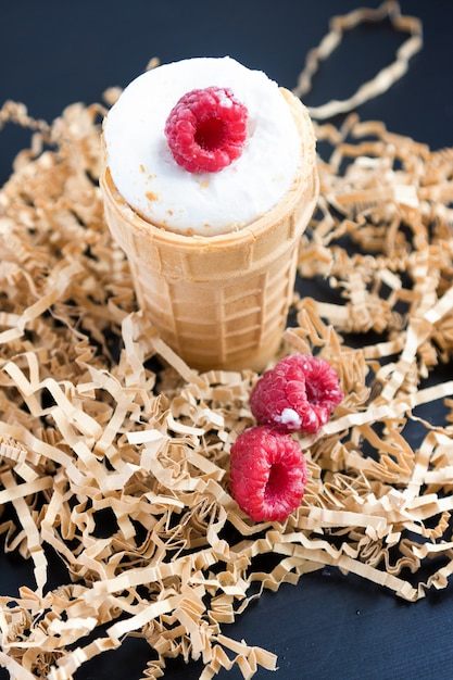 Ice cream with raspberry in waffle cone on wood Premium Photo