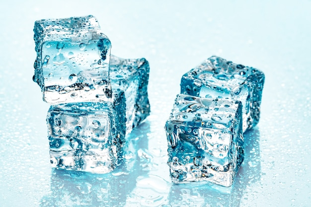 Ice cubes on blue background Premium Photo