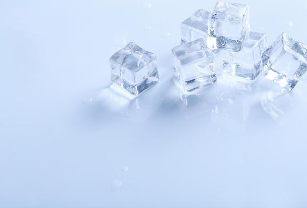 Cubetti di ghiaccio su superficie bianca con copyspace Foto Gratuite