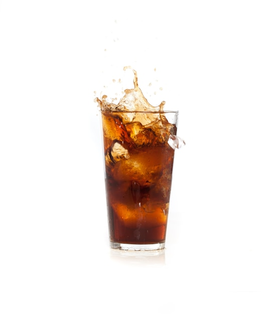 Ice falling in a brown drink Free Photo