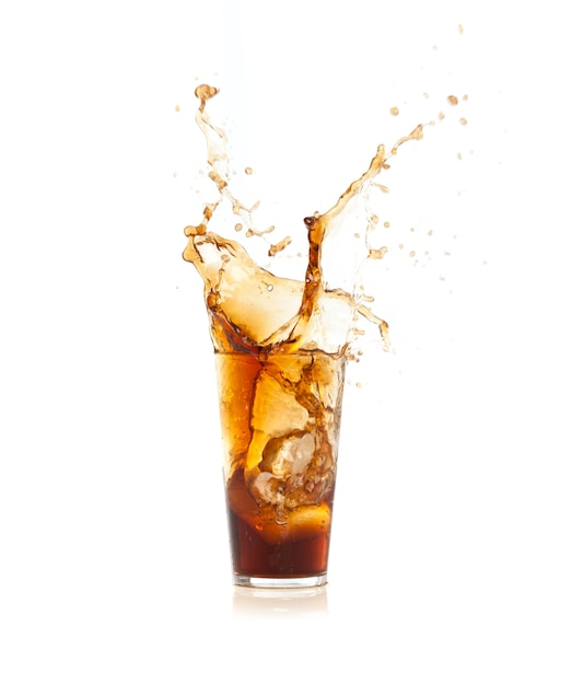 Ice falling into a glass with brown drink Free Photo
