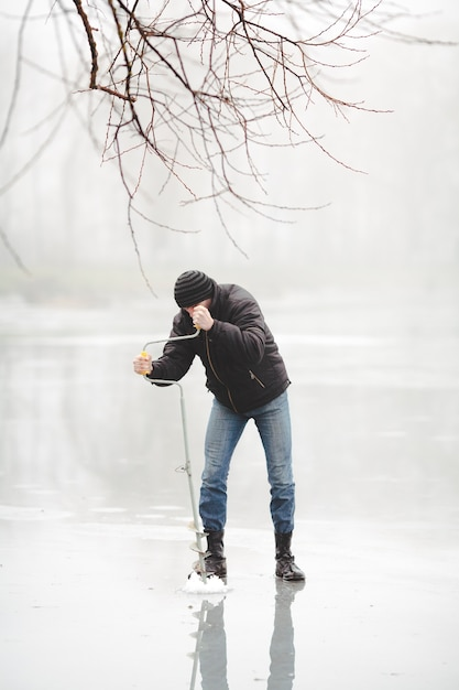 Ice fisherman drilling a hole with a power auger on frozen lake Free Photo